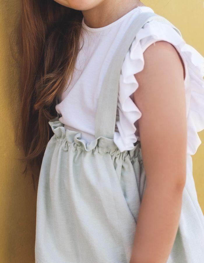 Falda El Tocador de Victoria, confeccionada en tejido con microraya en color lima. Con detalle de elástico alrededor de toda la cintura y tirantes ajustables en parte trasera mediante lazada.