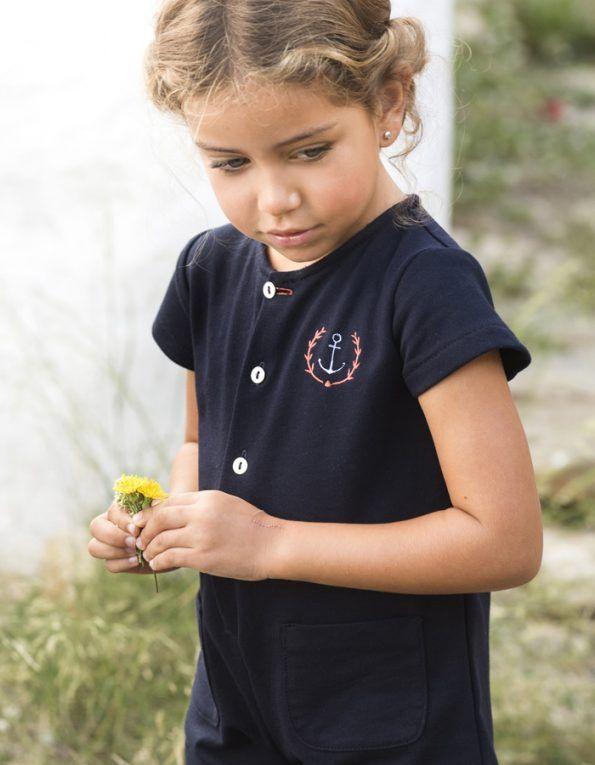 Mono Mi Canesú, confeccionado en tejido de algodón color azul marino, de pantalón corto y manga corta. Detalle de botonera delantera y bolsillos.