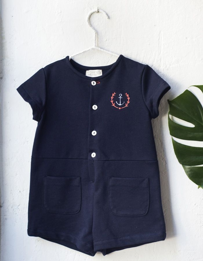 Jumpsuit Mi Canesú, made of navy blue cotton fabric, shorts and short sleeves. Detail of front keypad and pockets.