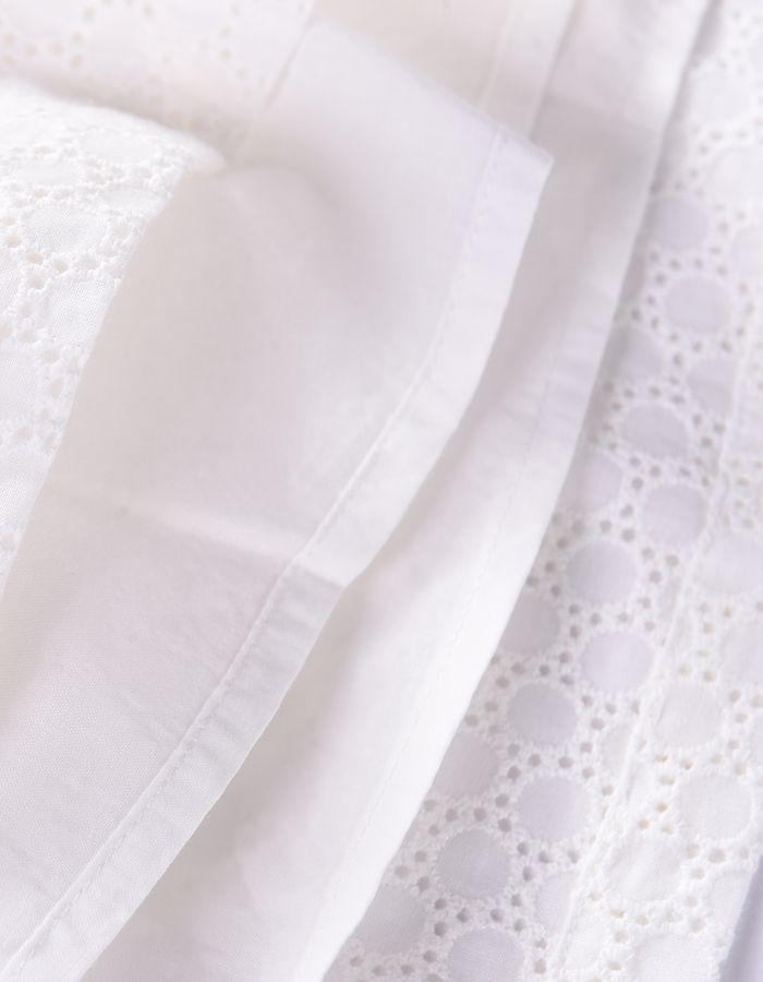 Vestido Louise Misha confeccionado en tejido brocado color blanco, con tirantes rematados en volantes cruzados en la espalda, bolsillos delanteros y detalle de borla rosa flúor en parte delantera.